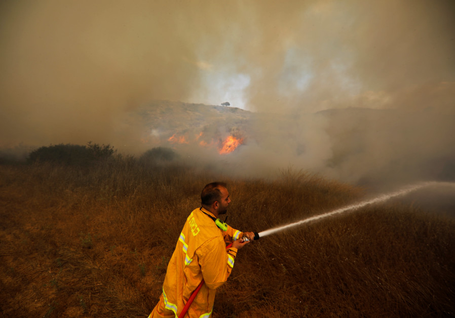 A firefighter attempts to extinguish a fire burning scrubland