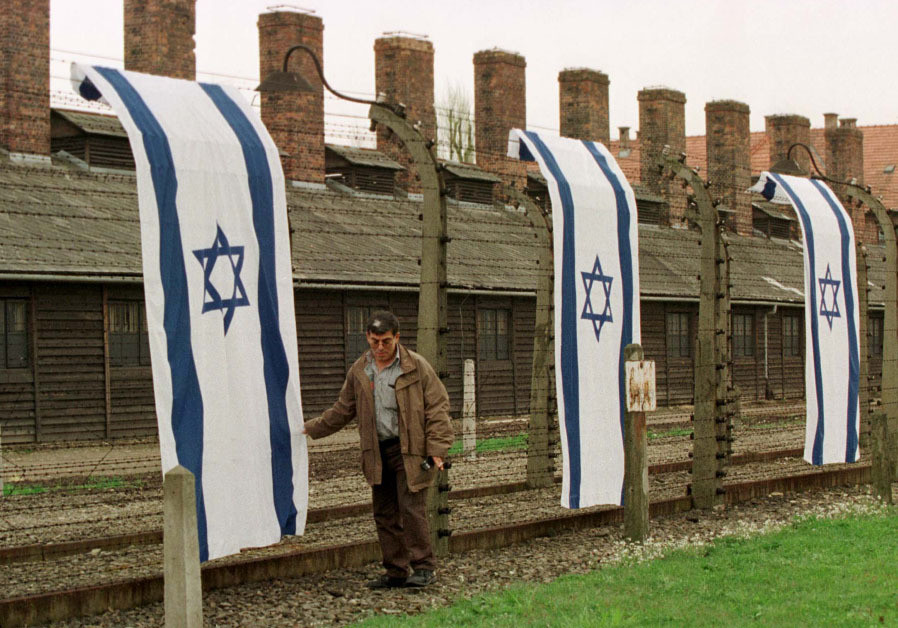 A MAN stands amid Israeli flags displayed outside Auschwitz in 1998.