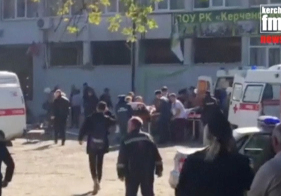 Emergency services carry an injured victim of a blast at at a college in the port city of Kerch