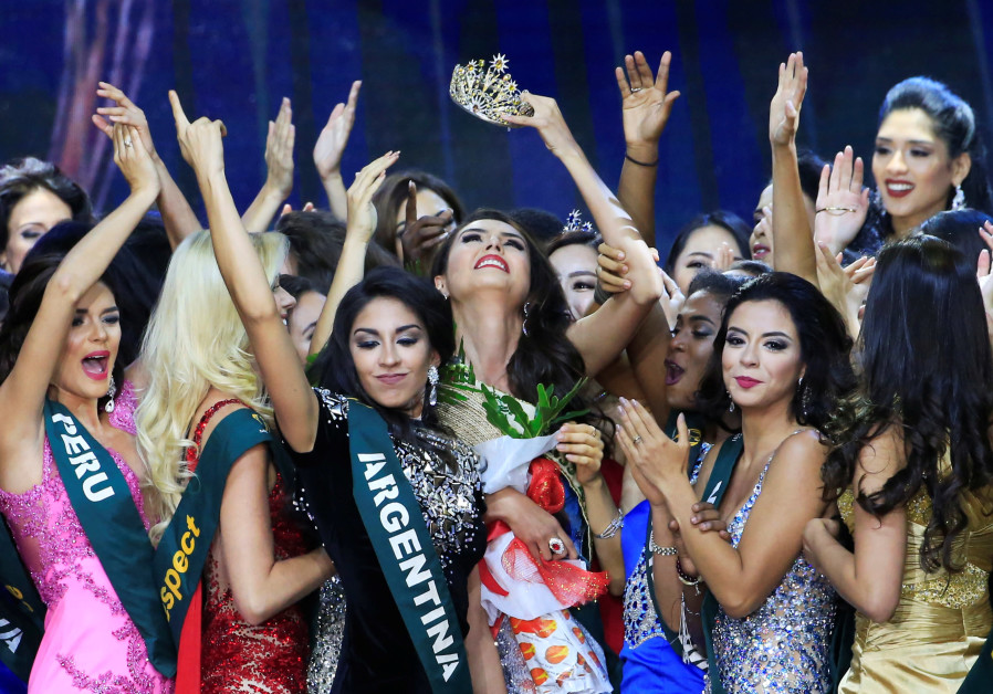 Miss Colombia Michelle Gomez (C), crowned 2016's Miss Earth Air, raises her crown