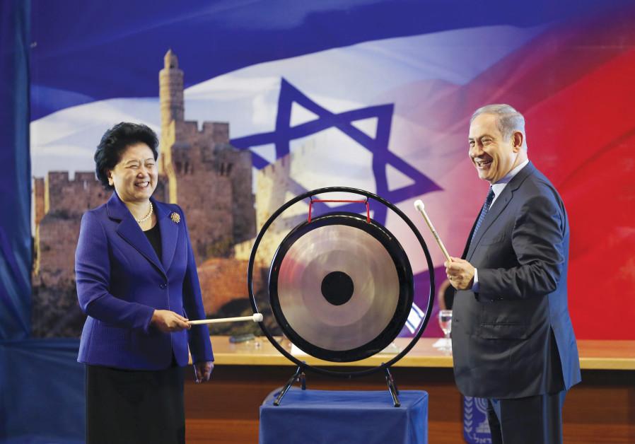 PRIME MINISTER BENJAMIN NETANYAHU and Chinese Vice Premier Liu Yandong strike a gong
