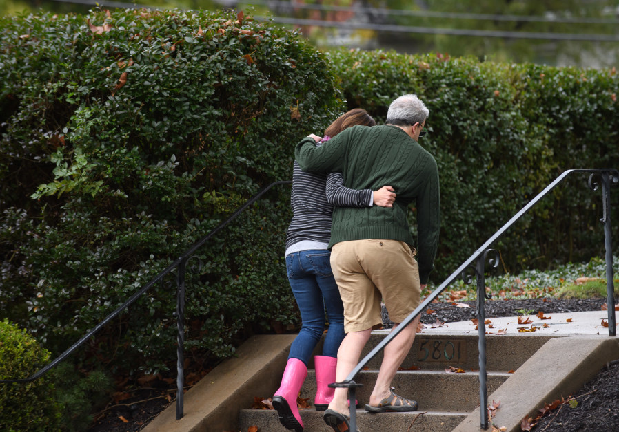 Neighbors around the corner from the site of a mass shooting at the Tree of Life Synagogue embrace