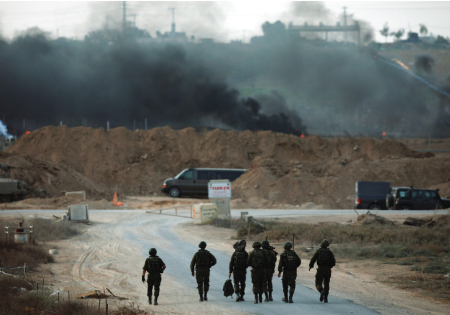 SOLDIERS WALK toward the border with the Gaza Strip