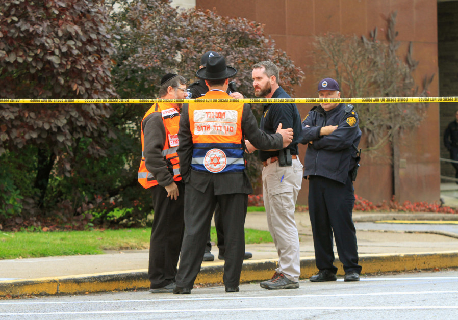 Police officers guarding the Tree of Life synagogue following shooting at the synagogue, speak with