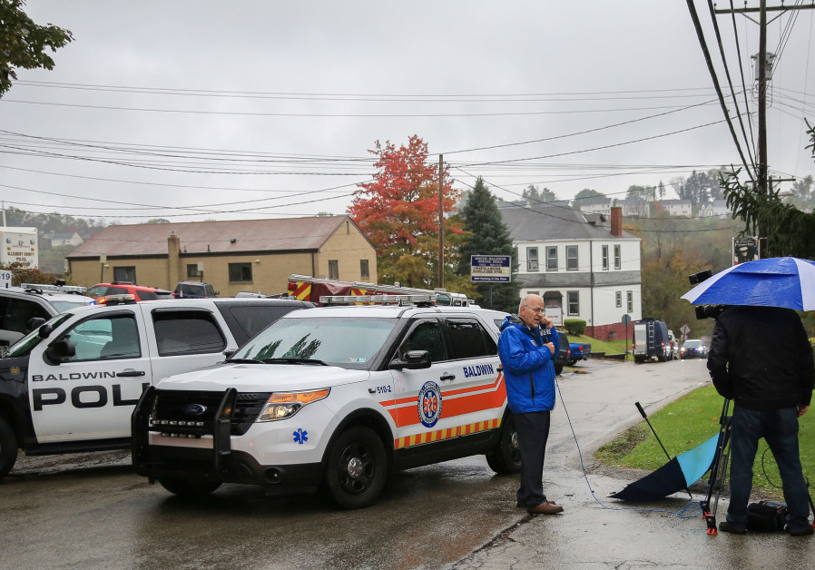 Police vehicles block off the road near the home of Pittsburgh synagogue shooting suspect