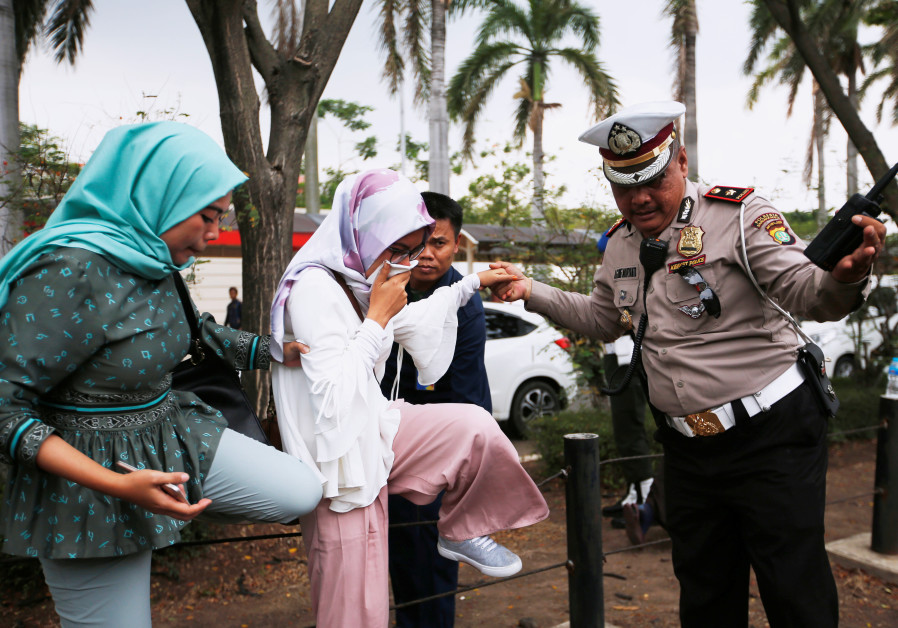 A policeman helps a woman who is a relative of a passenger of Lion A