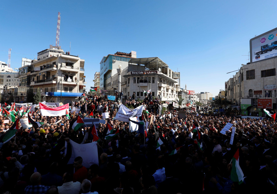 Palestinians take part in a protest against a social security law in Ramallah