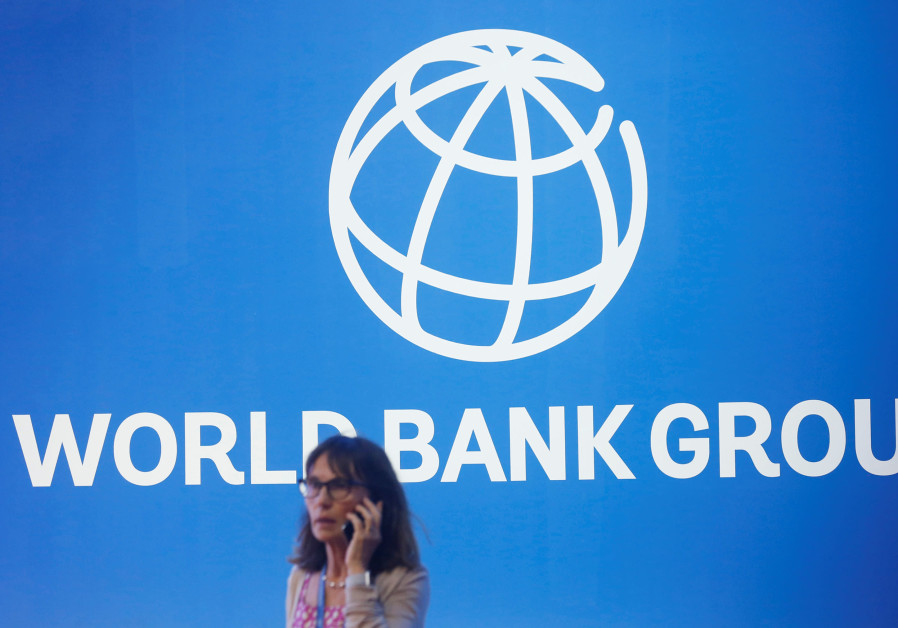 A participant stands near a logo of World Bank