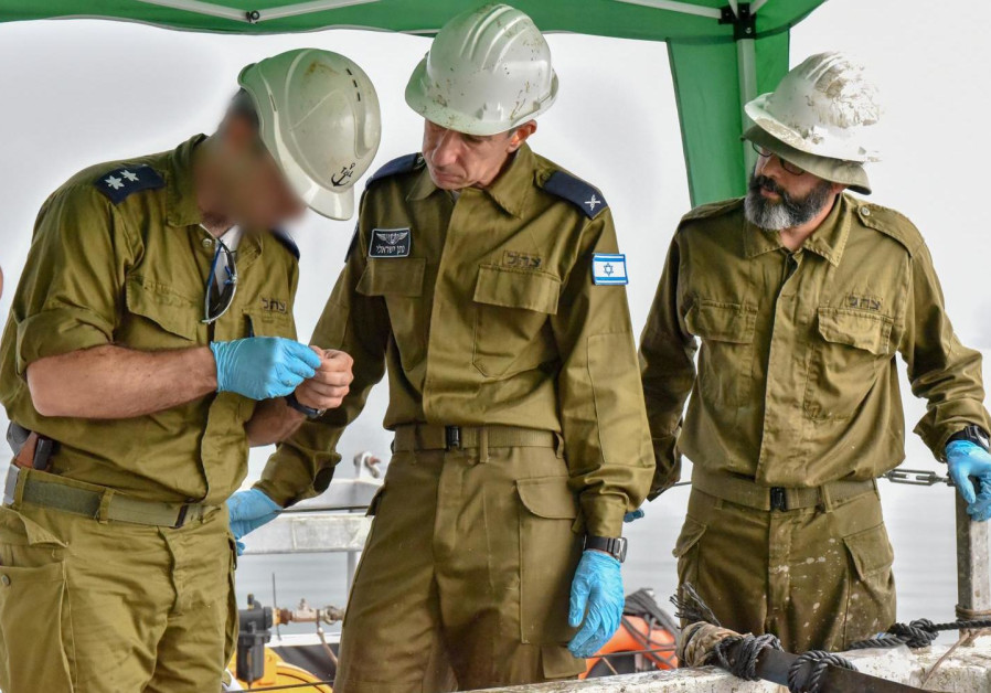 Offices from the Israeli Air Force review the remains of Yakir Naveh's plane.