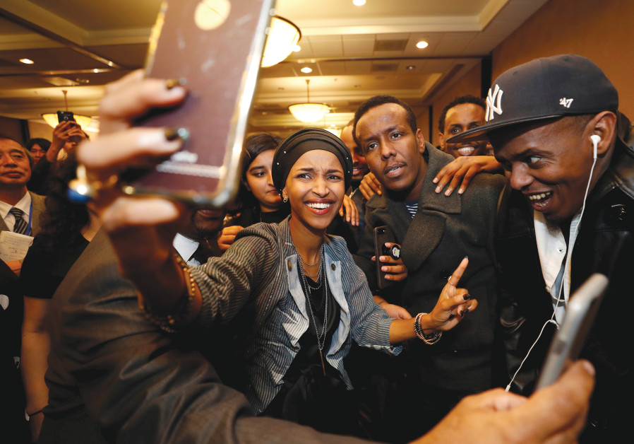 DEMOCRATIC CONGRESSIONAL candidate Ilhan Omar takes a selfie with supporters after appearing at her