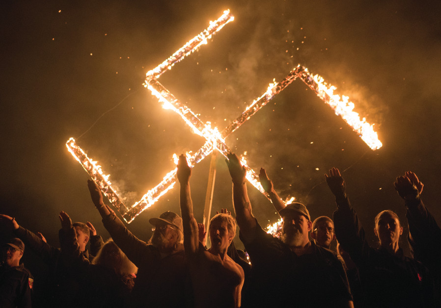 SUPPORTERS OF THE National Socialist Movement give Nazi salutes while taking part in a swastika-burn