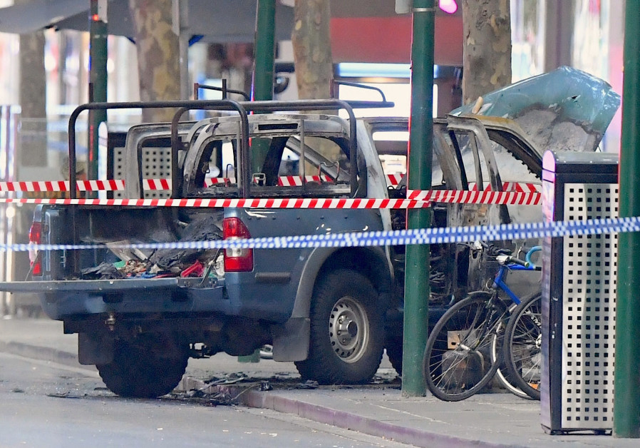 A burnt out vehicle is surrounded by police tape on Bourke Street in central Melbourne, 2018.