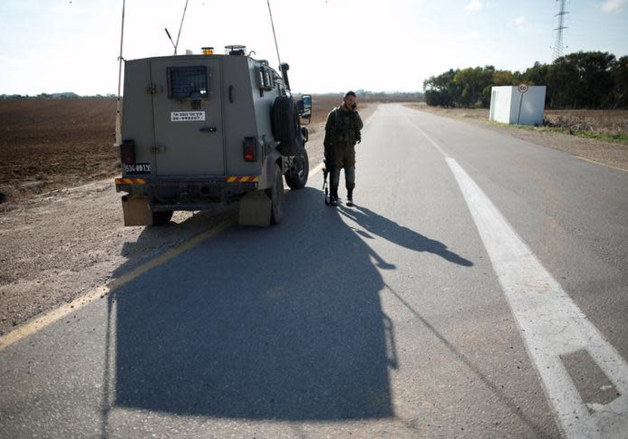 An IDF soldier stands next to an armored vehicle in Kibbutz Nahal Oz, near the Gaza Strip border