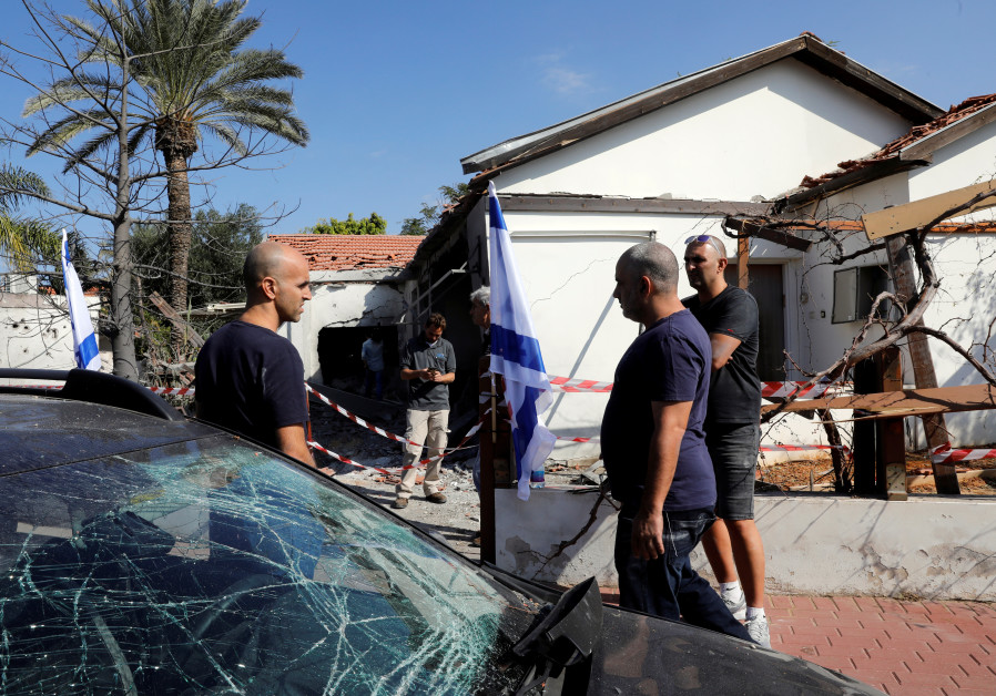 People stand next to a car and house damaged by a rocket fired from the Gaza Strip, in the Israeli c