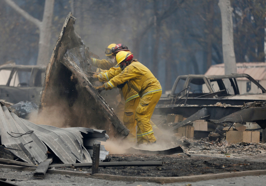 Cal Fire firefighters comb through a house destroyed by the Camp Fire in Paradise