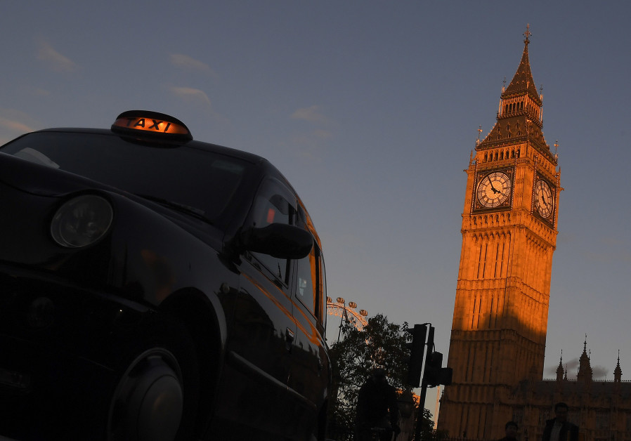 A London black cab taxi drives past Big Ben and the Houses of Parliament in late afternoon sunlight