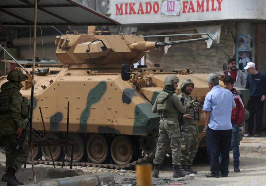 People speak with Turkish soldiers in the center of Afrin