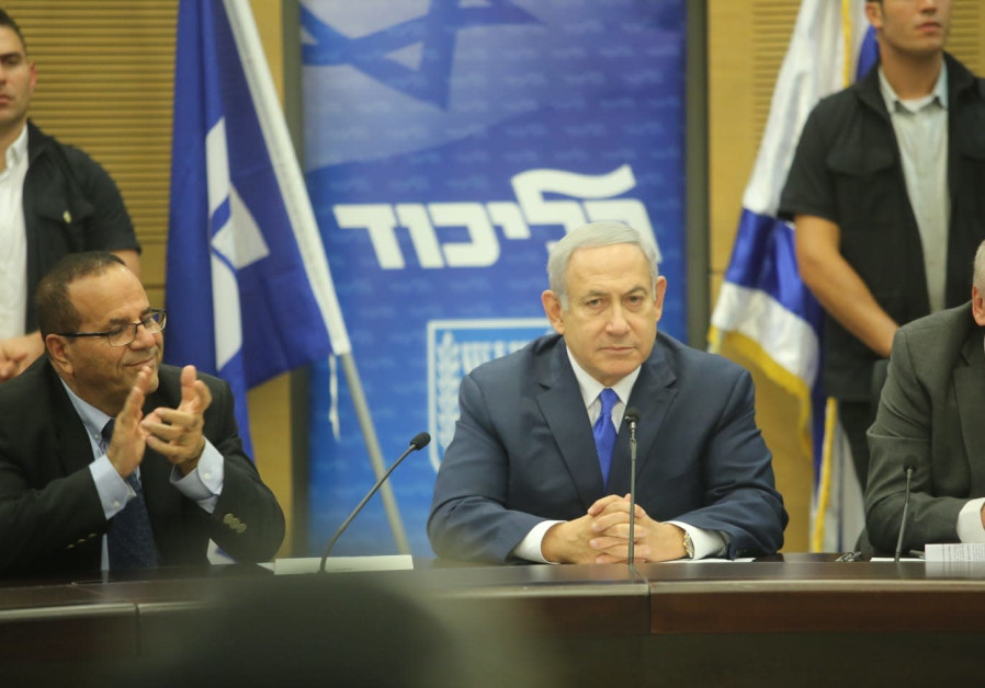 Prime Minister Benjamin Netanyahu (C) receives applause at a weekly faction meeting