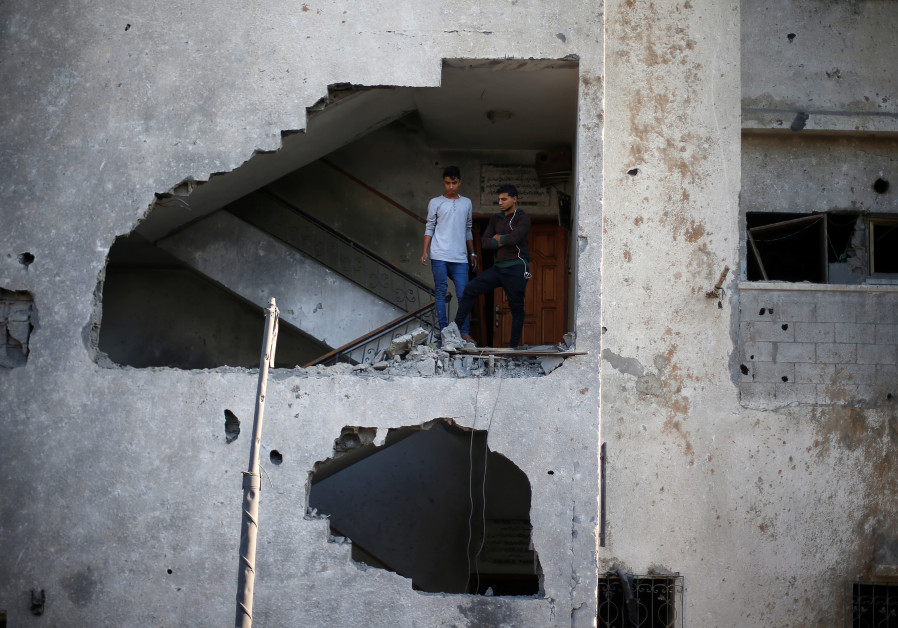 Palestinians look out of their house that was damaged in an Israeli air strike, in Gaza City Novembe