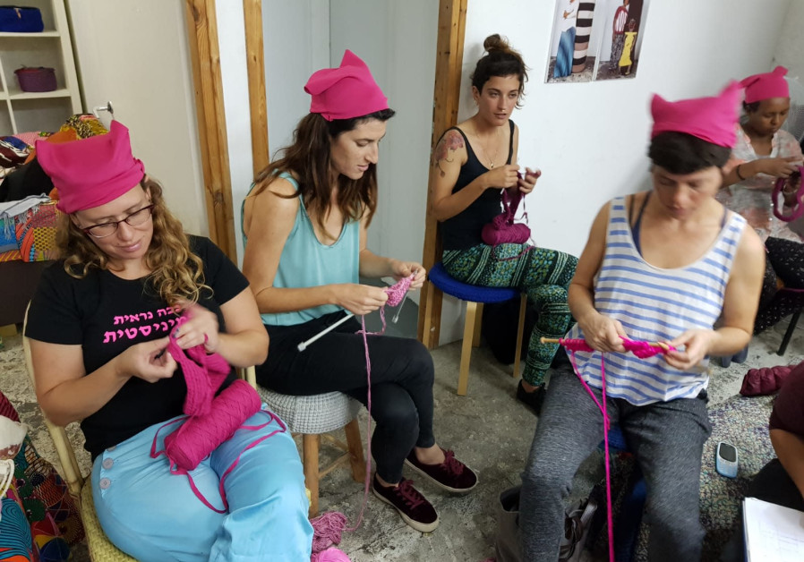 Women knit pink hats with member of the Kuchinate, the African Refugee Women's Collective, in south