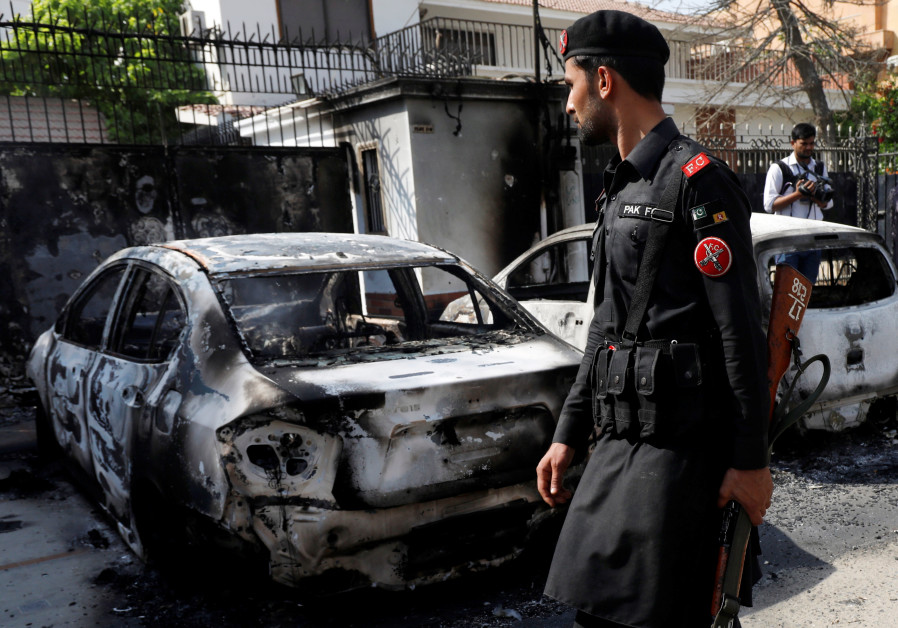A paramilitary soldier walks past car wreckages after an attack on Chinese consulate, Pakistan, 2018