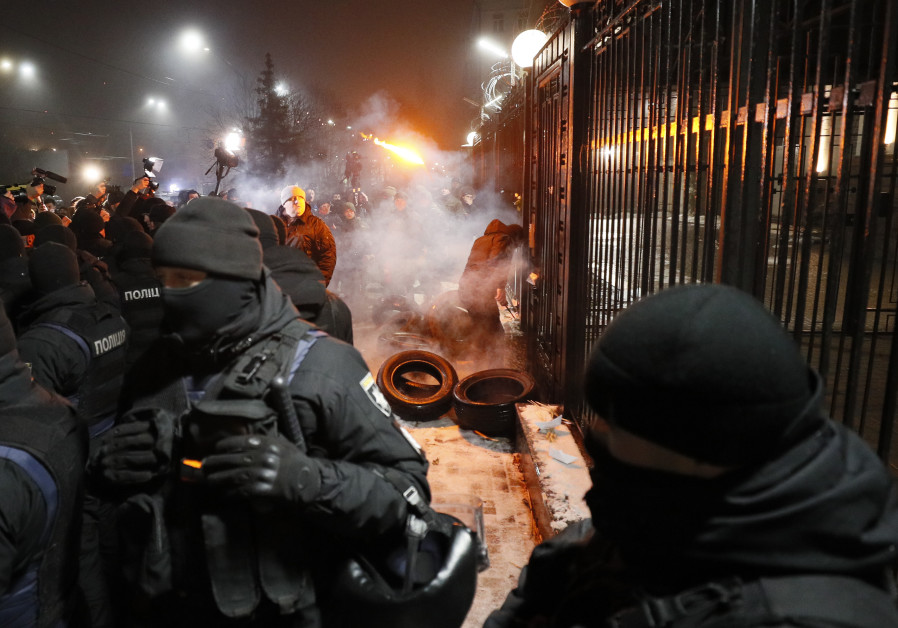 A National Guard serviceman extinguishes a torch thrown by a protester during a rally.