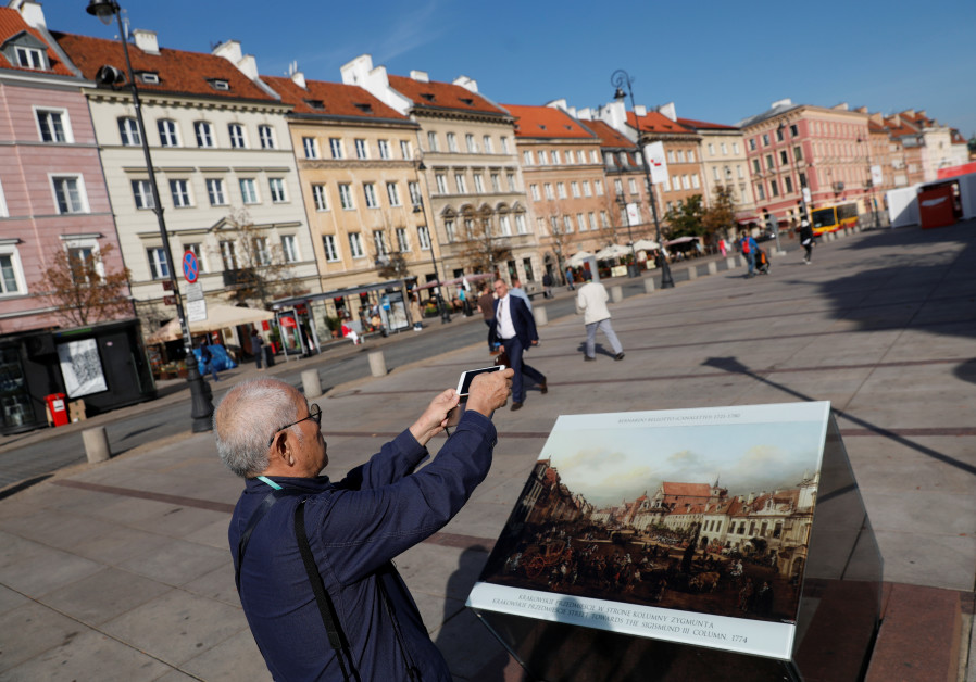 A tourist takes a picture at the Old Town in Warsaw, Poland September 17, 2018.