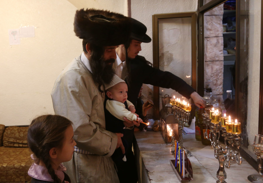 Lighting Hanukkah candles in Jerusalem's Mea She'arim neighborhood