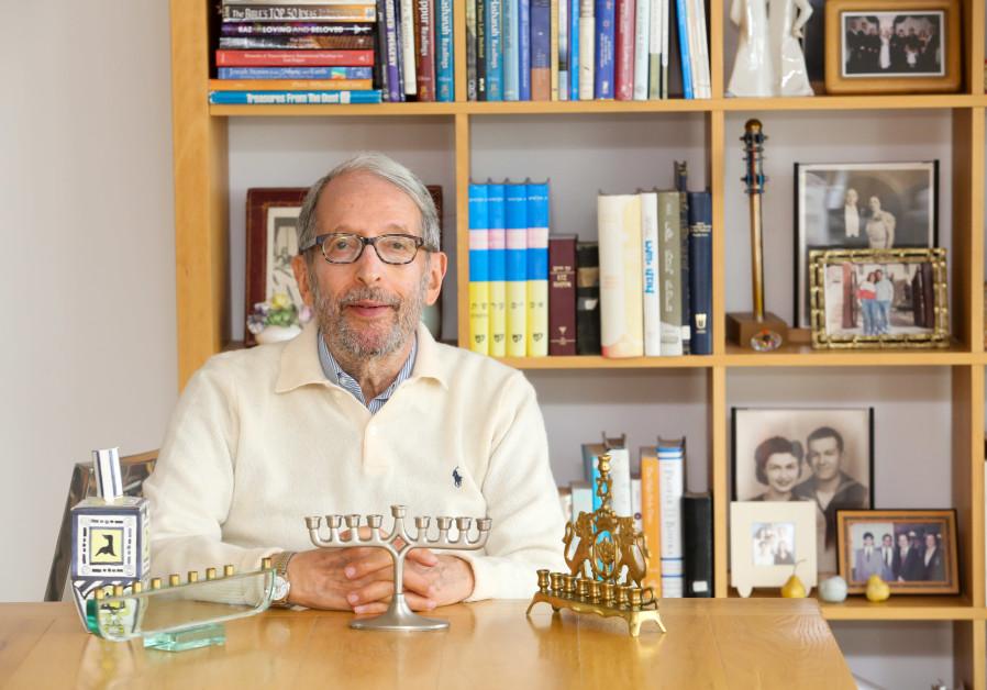 Rabbi Dov Peretz Elkins shows off several of his hanukkiot in his Jerusalem apartment