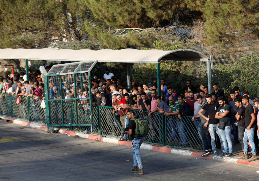 An Israeli security guard walks as Palestinian workers wait to cross into Barkan industrial zone tha