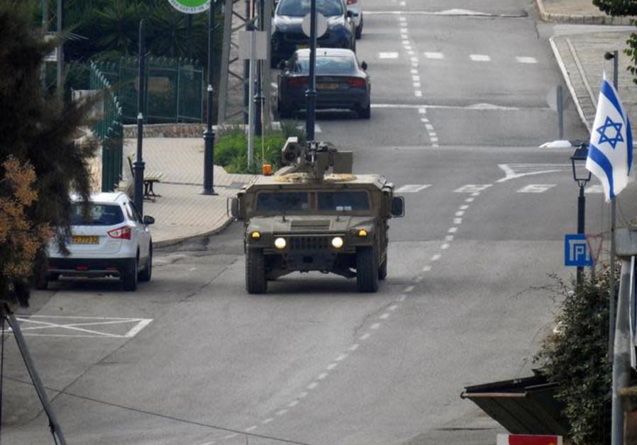 An Israeli vehicle patrols a street in Metulla, Israel, as seen from the village of Kfar Kila