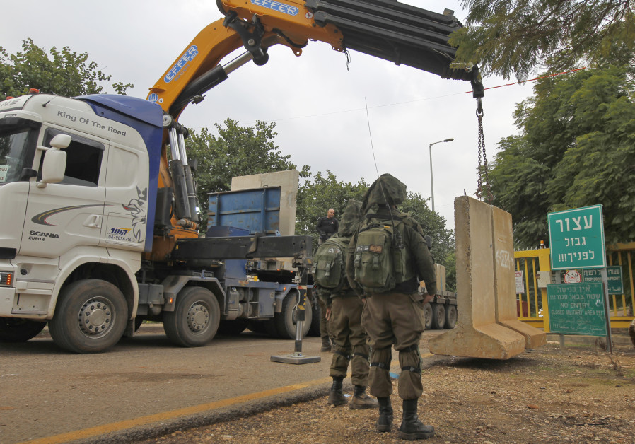 a crane laying a concrete T-wall block at a security checkpoint along a road