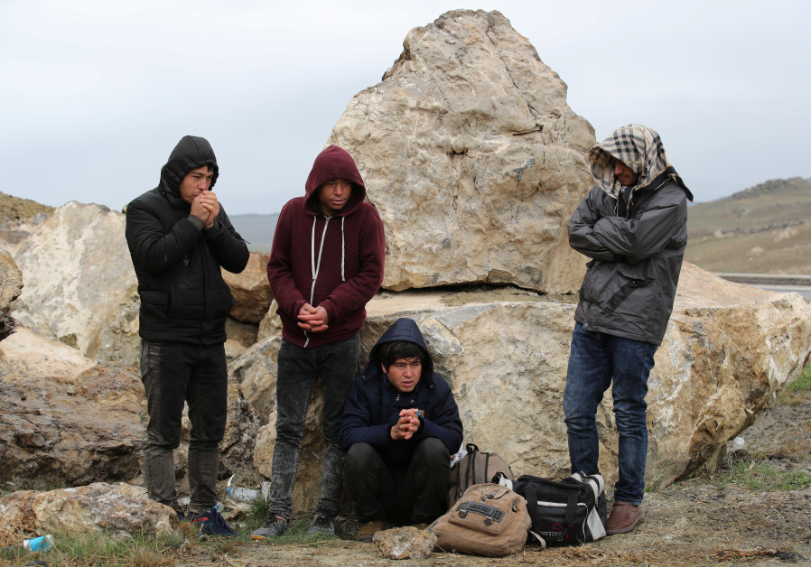 A group of Afghan migrants rest, during a break from their walk, on a main road, after crossing the