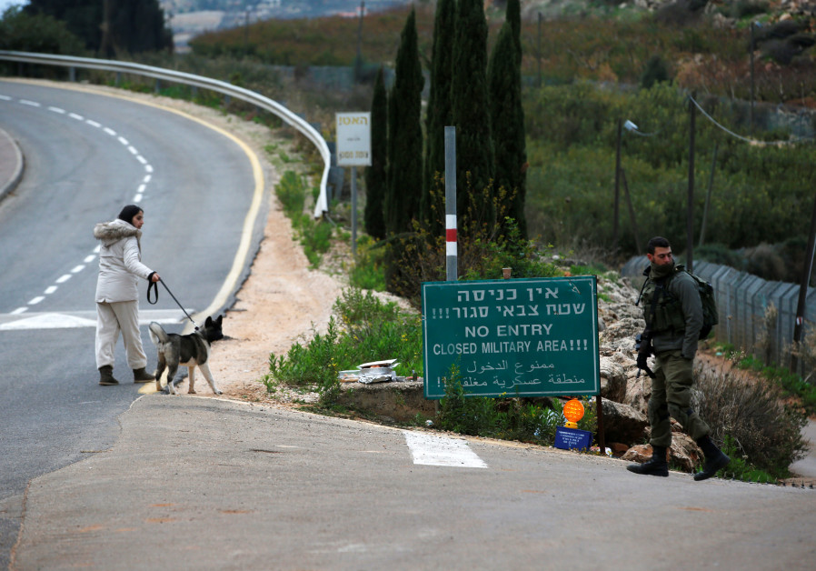 A woman walks her dog as an Israeli soldier guards near the border with Lebanon