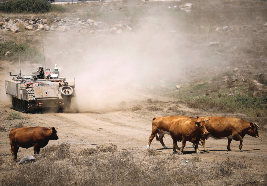 AN ARMORED VEHICLE rides during an army drill to the Israeli side of the Golan Heights in August.