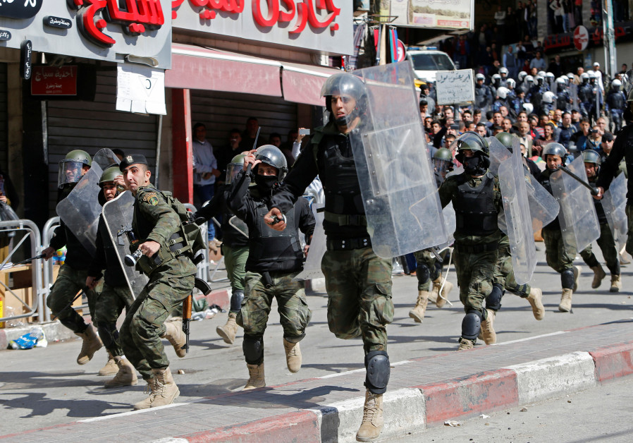 Members of the Palestinian security forces clash with demonstrators during a protest organised by Hi