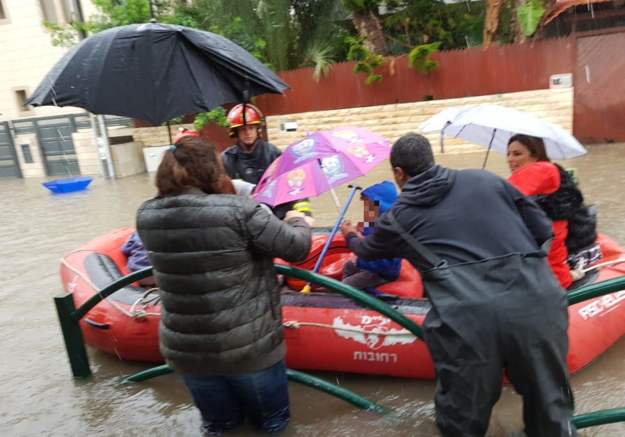 Children are rescued from a flooded kindergarden in Rehovot on December 6, 2018