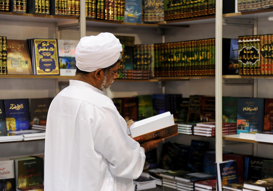 A handout picture released by the Qatari ministry of culture shows a man browsing through a book