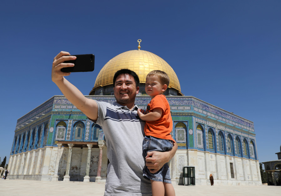 A Muslim tourist holds a child as he takes a selfie photo in front of the Dome of the Rock