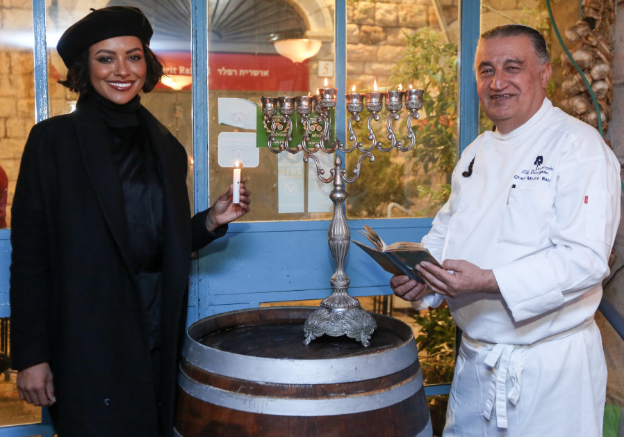 Actress Kat Graham and Eucalpytus chef Moshe Basson light candles for Hanukkah at the restaurant in