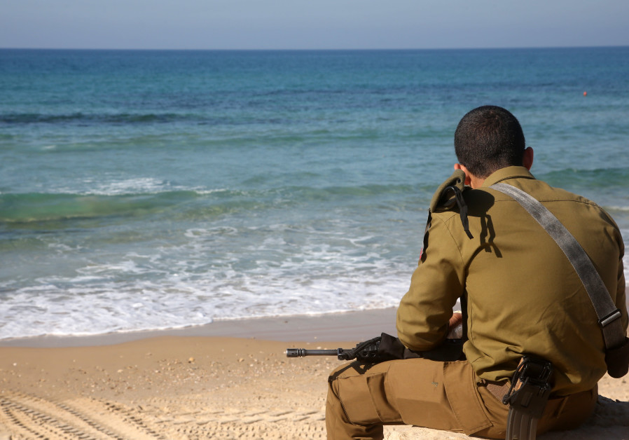 An IDF soldier sits on a beach in Tel Aviv