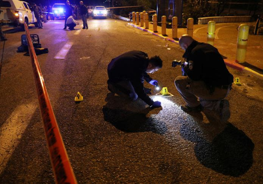 Israeli security forces and emergency personnel work at the scene of shooting attack