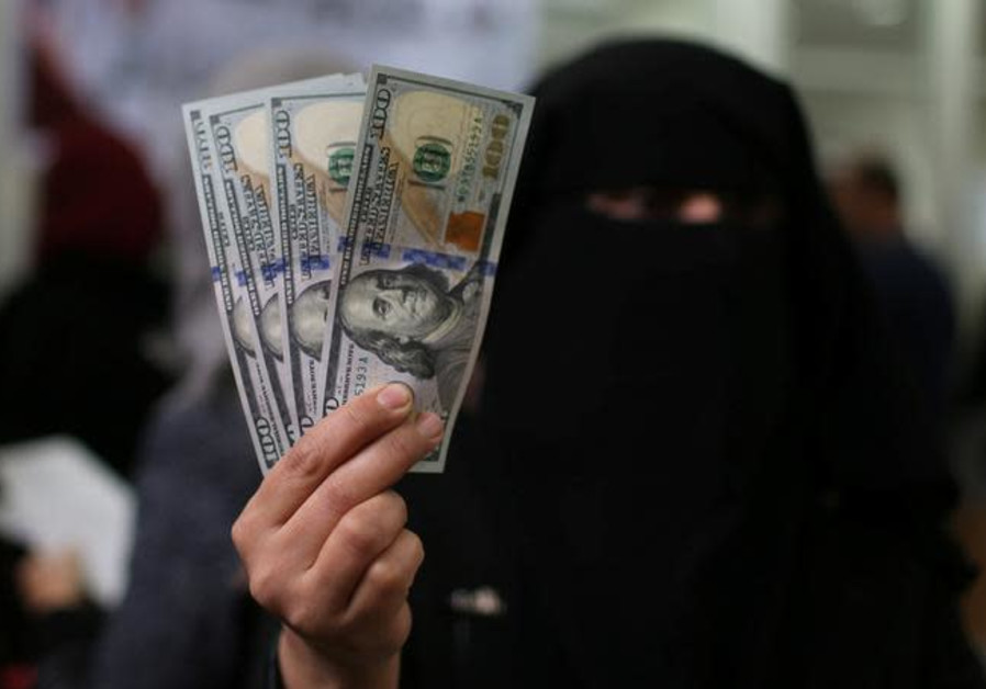 A Palestinian Hamas-hired civil servant displays U.S. Dollar banknotes
