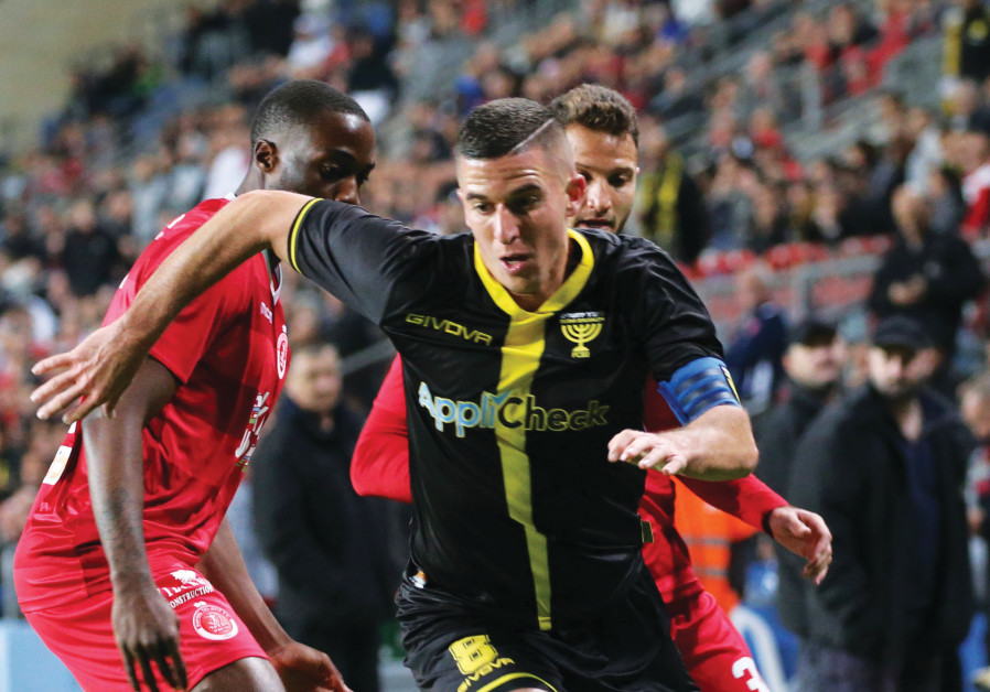 BEITAR JERUSALEM forward Idan Vered dribbles past a pair of Hapoel Tel Aviv defenders during Beitar'