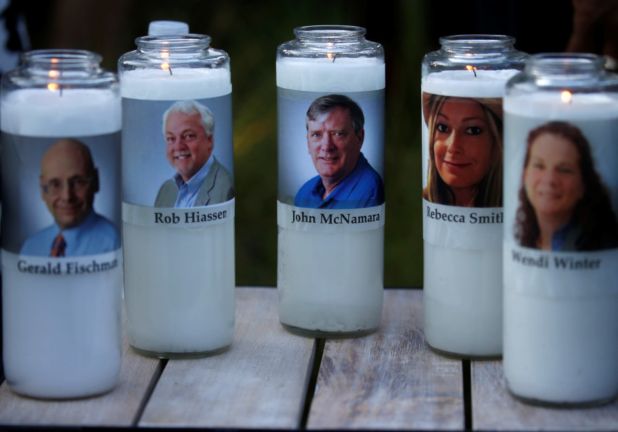 Candles representing the slain journalists of Capital Gazette sit on display during a candlelight vi