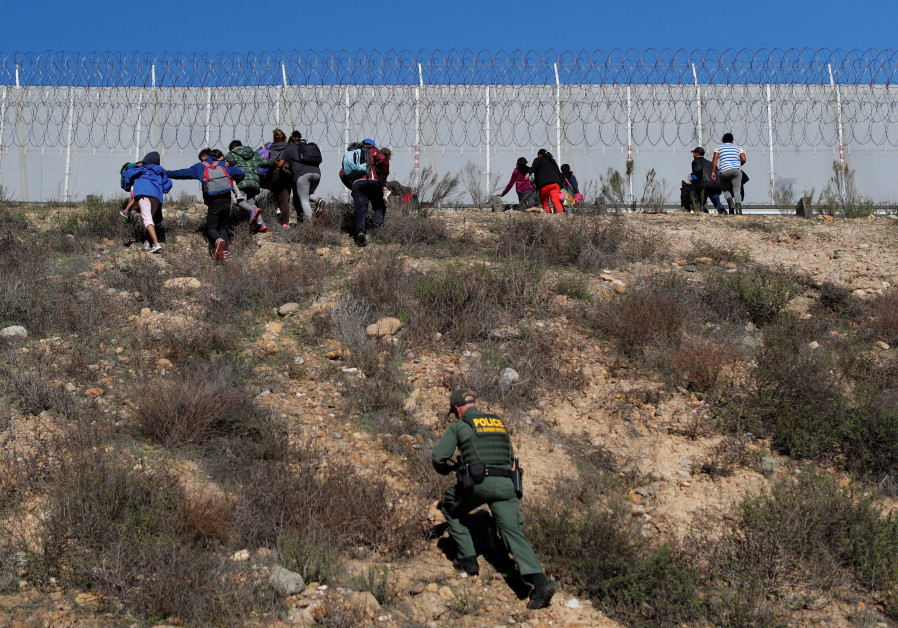U.S. Customs and Border Protection (CBP) officials detain a group of migrants, part of a caravan of