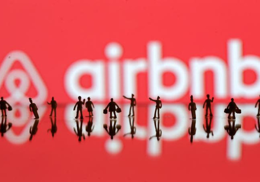A 3D printed people's models are seen in front of a displayed Airbnb logo in this illustration taken