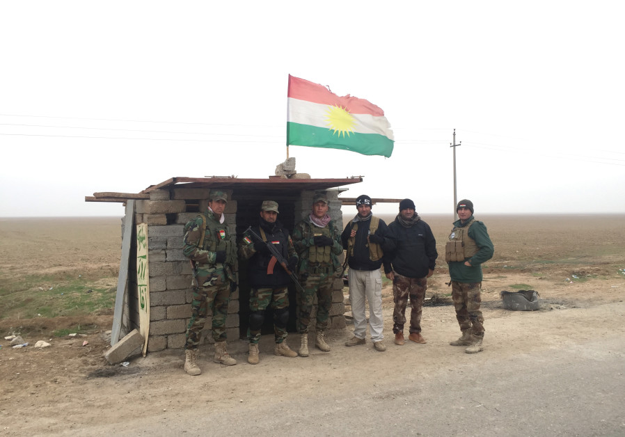 ROJAVA PESHMERGA troops guard a road in northern Iraq in December 2015.