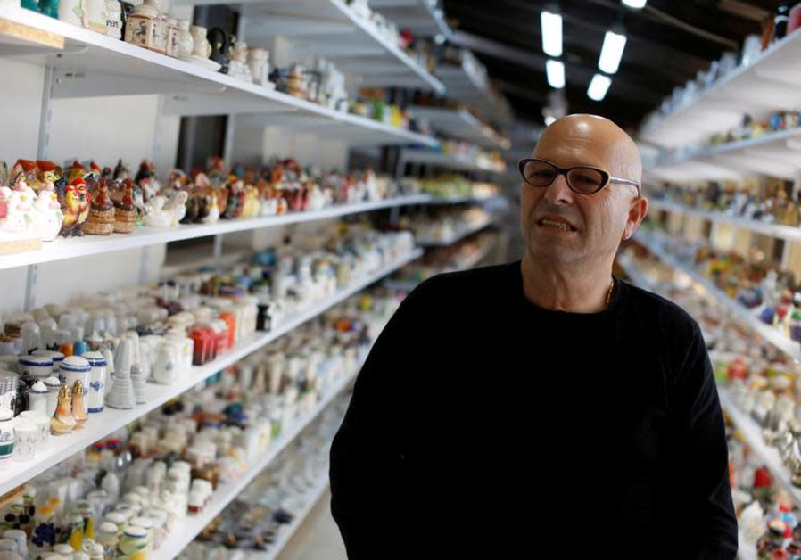 Eitan Bar-on stands next his collection of 37,000 pairs of shakers, displayed in a shack at the back