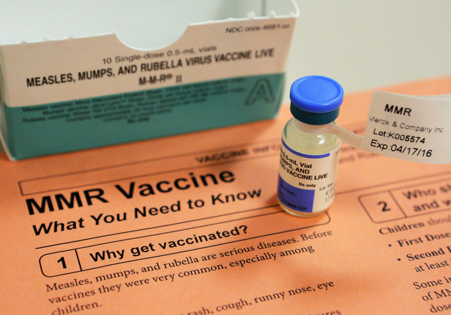 A vial of measles, mumps and rubella vaccine and an information sheet.